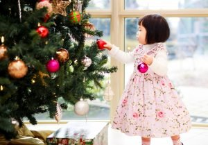 Children decorating a Christmas tree.em of their lost loved one.