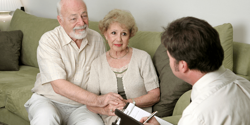 funeral director speaking with an elderly couple
